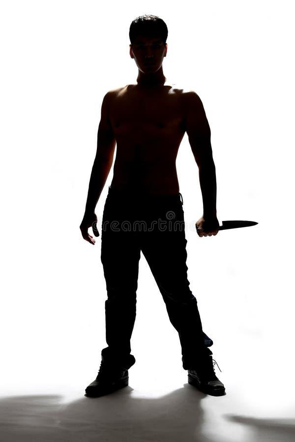 Silhouet van een mes van de mensenholding stock foto's
