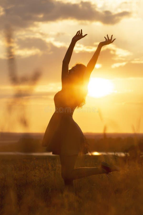 Silhouet van een mooi dromerig meisje bij zonsondergang op een gebied, een jonge vrouwenidance met geluk op aard royalty-vrije stock afbeeldingen