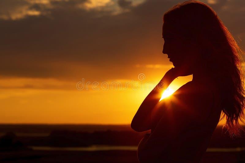 Silhouet van een mooi romantisch meisje bij zonsondergang, gezichtsprofiel van jonge vrouw met lang haar in heet weer stock foto