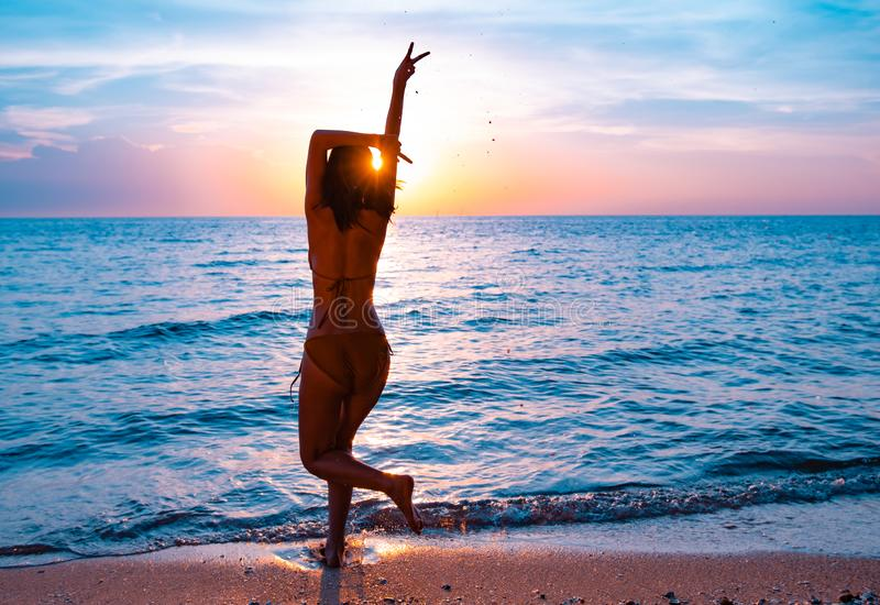 Silhouet van een mooi, slank meisje dat op een achtergrond van een zonsondergang springt royalty-vrije stock fotografie