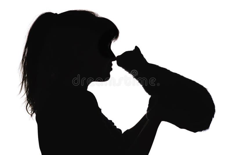 Silhouet van een mooie het profielneus van het vrouwengezicht aan neus met een klein katje in haar wapens, het concept het geven  royalty-vrije stock afbeeldingen