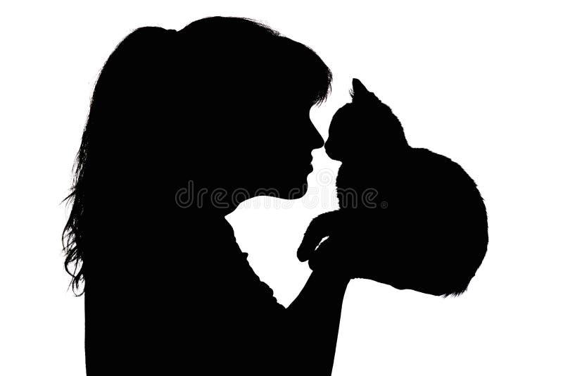 Silhouet van een mooie vrouw dat aan neus met een klein katje in haar wapens, het concept het geven voor dieren, favoriet huisdie royalty-vrije stock foto's