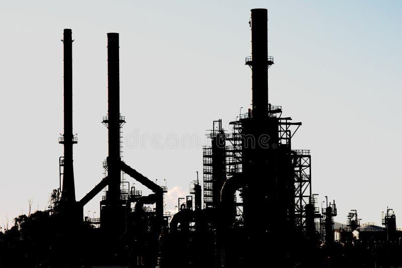 Silhouet van een olieraffinaderij met schoorstenen royalty-vrije stock foto