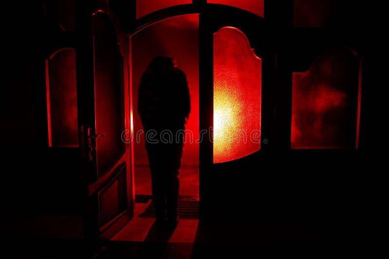 Silhouet van een onbekend schaduwcijfer aangaande een deur door een gesloten glasdeur Het silhouet van een mens voor een venster  stock illustratie