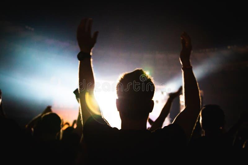 Silhouet van een overlegmenigte Het publiek juicht de musici op stadium toe De heldere schijnwerper en de dansende mensen stock fotografie