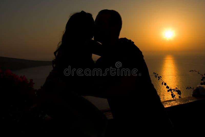 Silhouet van een paar dat bij Zonsondergang kust stock afbeeldingen