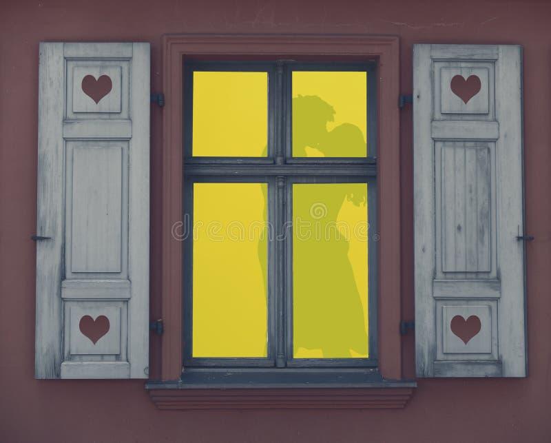Silhouet van een paar die liefde in een aangestoken raamkozijn, een romantische nacht, het concept van de valentijnskaartendag ma royalty-vrije illustratie