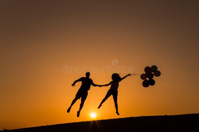Silhouet van een paar die met ballons bij zonsondergang spelen stock foto's
