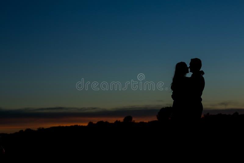 Silhouet van een paar met een mooie zonsondergang royalty-vrije stock foto's