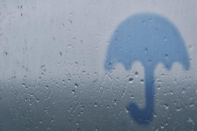 Silhouet van een paraplu op een achtergrond van glas met dalingen en regendruppels royalty-vrije stock afbeelding