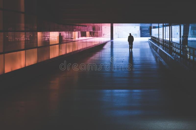 Silhouet van een persoon die in een donkere tunnel lopen stock afbeelding