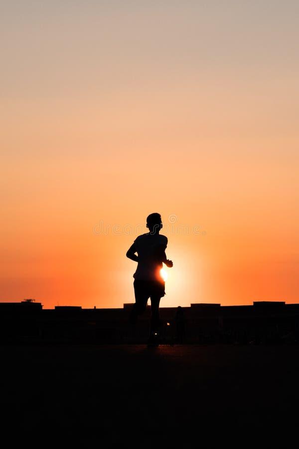 Silhouet van een persoon die naar de achtergrond van de zonsonderganghemel lopen royalty-vrije stock foto's