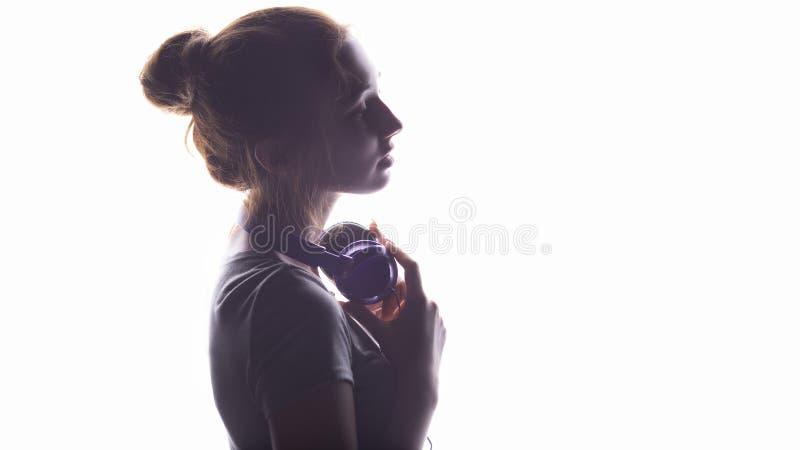 Silhouet van een romantisch meisje die aan muziek in hoofdtelefoons, het jonge vrouw ontspannen op een witte achtergrond luistere stock foto's