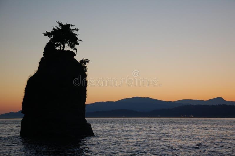 Silhouet van een rots op de oceaan stock foto's