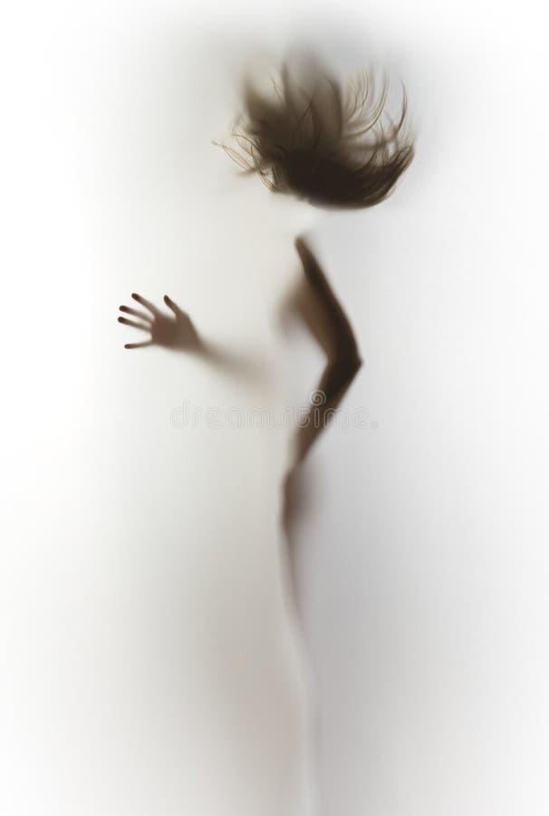 Silhouet van een slank, menselijk lichaam van een vrouw, vliegend haar, hand, vingers stock foto's