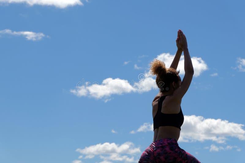 Silhouet van een sportief donker-gevild meisje tegen de hemel met wolken Een jonge Afrikaans-Amerikaan is bezig geweest met gesch royalty-vrije stock foto's
