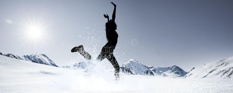 Silhouet van een springende vrouw in Sneeuwbergen royalty-vrije stock afbeelding
