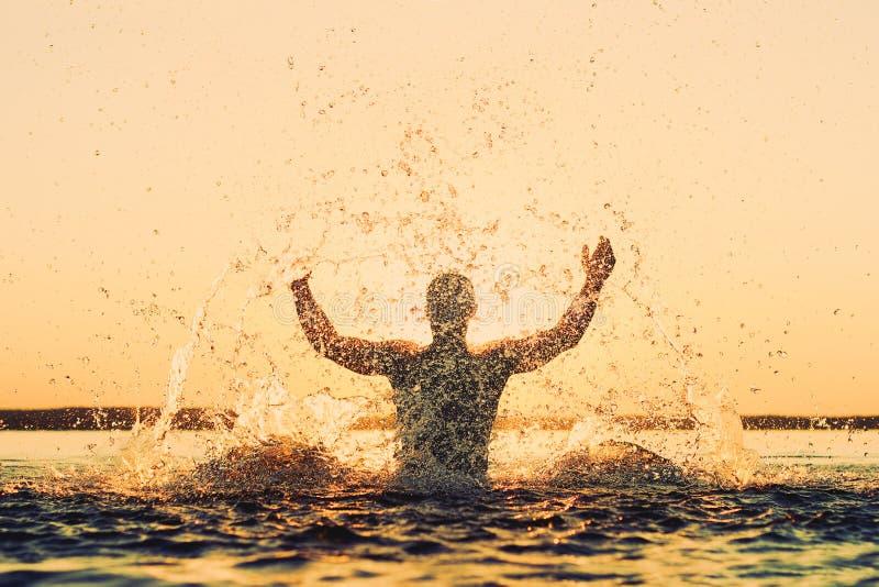 Silhouet van een sterke mens in een nevel van water bij zonsondergang royalty-vrije stock foto
