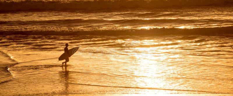 Silhouet van een surfer bij zonsondergang op de Atlantische Oceaan in Lacanau Frankrijk, panorama en branding stock afbeeldingen