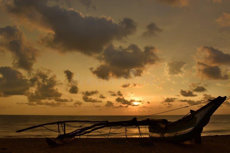 Silhouet van een traditionele vissersboot bij zonsondergang Negombo Sri Lanka stock foto's