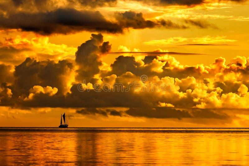 Silhouet van een varende boot bij dramatische gouden zonsondergang stock foto's