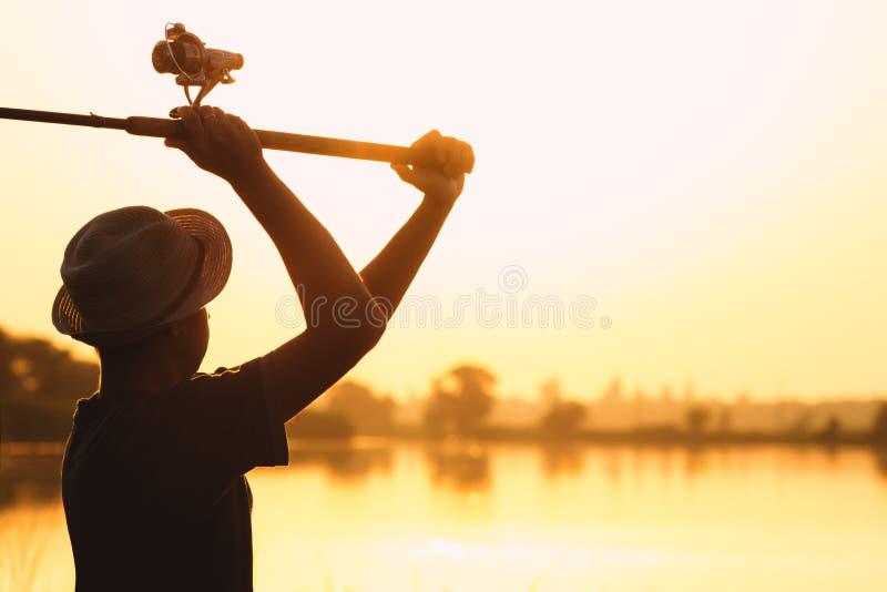 Silhouet van een vissende mens bij dageraad royalty-vrije stock afbeelding