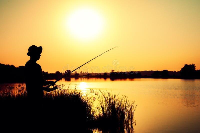 Silhouet van een vissende mens op de rivierbank op de aard stock afbeeldingen