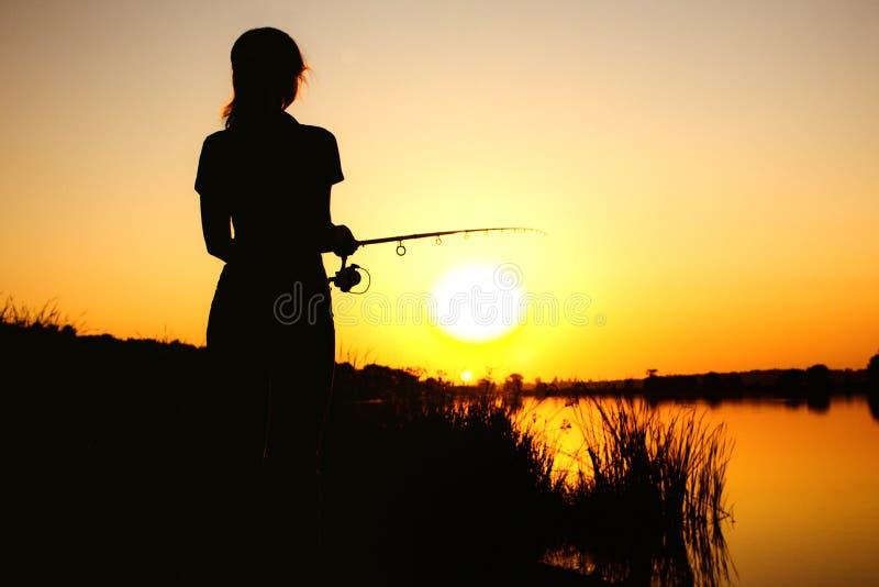 Silhouet van een vissende vrouw op de rivierbank op de aard bij dageraad royalty-vrije stock foto's