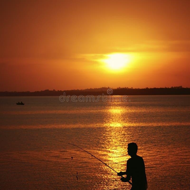 Silhouet van een visser en zijn hengel tijdens zonsondergang stock afbeelding