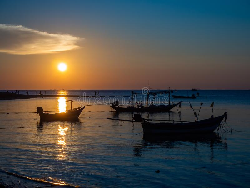 Silhouet van een vissersboot in de stralen van de het plaatsen zon met wolken stock afbeeldingen
