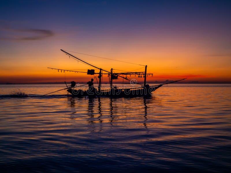 Silhouet van een vissersboot in de stralen van de het plaatsen zon met wolken royalty-vrije stock afbeelding