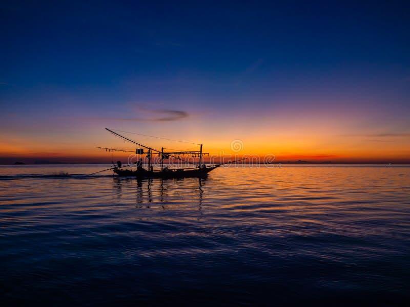 Silhouet van een vissersboot in de stralen van de het plaatsen zon met wolken royalty-vrije stock foto