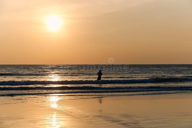 Silhouet van een vissersmens tegen de zonsondergang en het overzees zandstrand en golf, met warme kleuren wordt gekleurd die stock foto's