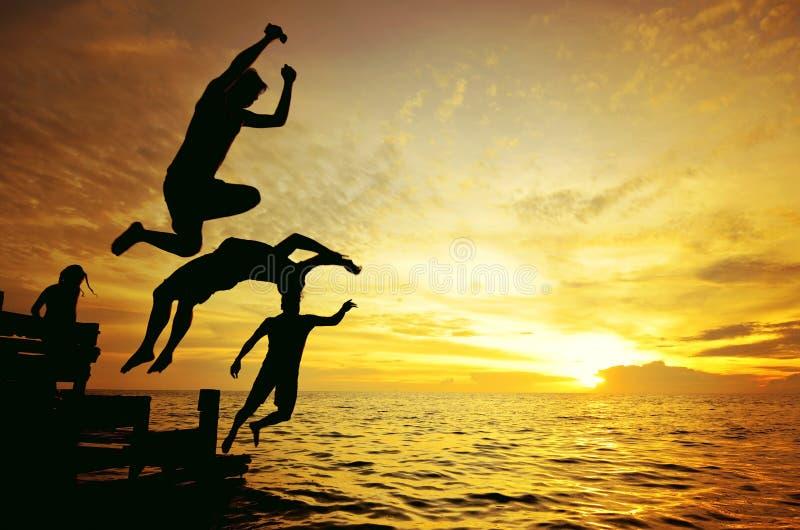 Silhouet van een vriend die in het overzees tijdens gouden zonsondergang springen stock foto's