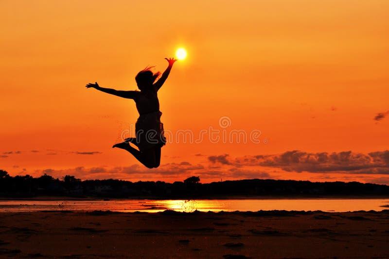 Silhouet van een vrouw die bij zonsondergang, het raken springen stock afbeeldingen