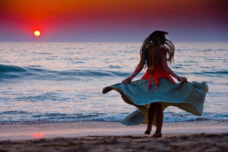 Silhouet van een vrouw die door de oceaan bij zonnen danst stock afbeelding
