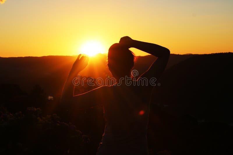 Silhouet van een vrouw die op de zonsondergang letten royalty-vrije stock fotografie