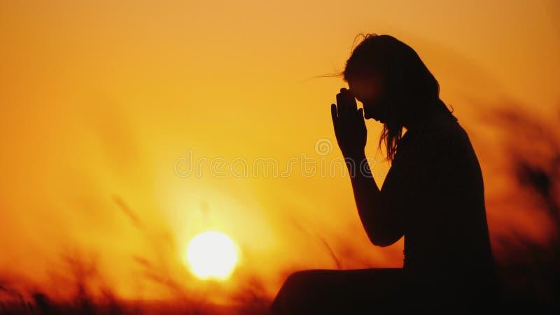 Silhouet van een vrouw die tegen de achtergrond van een oranje hemel en een grote het plaatsen zon bidt royalty-vrije stock afbeelding