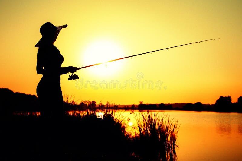 Silhouet van een vrouw in een hoed belast met sport visserij stock foto's