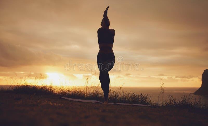 Silhouet van een vrouw het praktizeren yoga, Garudasana royalty-vrije stock fotografie