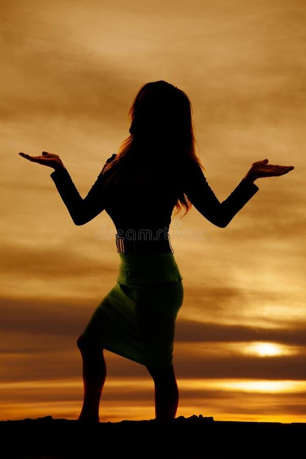 Silhouet van een vrouw in kledingshanden omhoog royalty-vrije stock foto