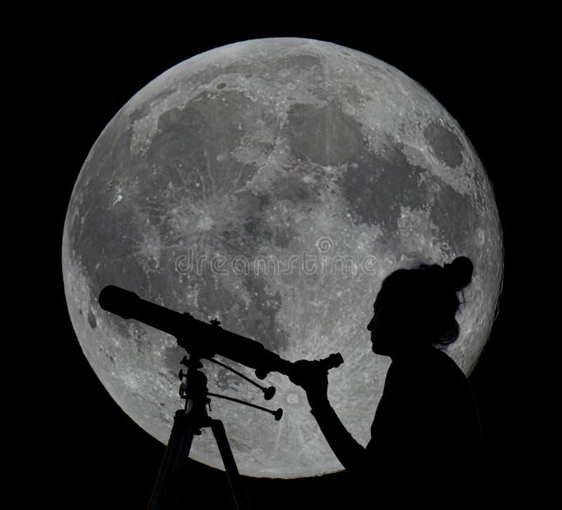 Silhouet van een vrouw met telescoopmaan het Waarnemen stock foto