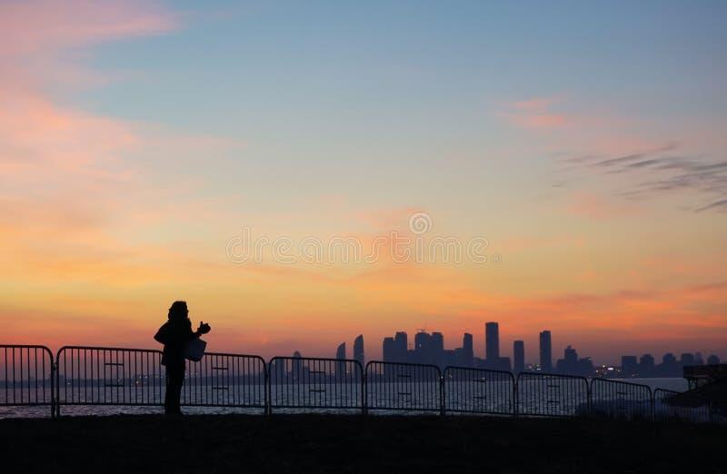 Silhouet van een vrouw over het bekijken de horizon zonsondergang stock afbeelding