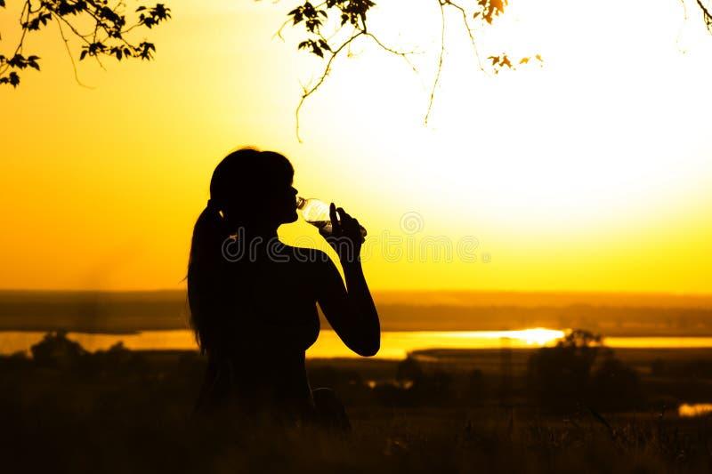 Silhouet van een vrouwen drinkwater na lichaamsbeweging in aard, meisjesprofiel bij zonsondergang, concept sport en ontspanning stock fotografie
