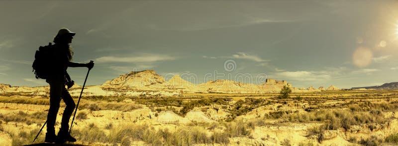 Silhouet van een vrouwentrekking in een woestijn stock afbeeldingen