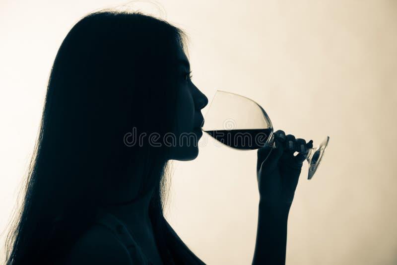 Silhouet van een wijfje wordt geschoten die rode wijn drinken die stock afbeeldingen