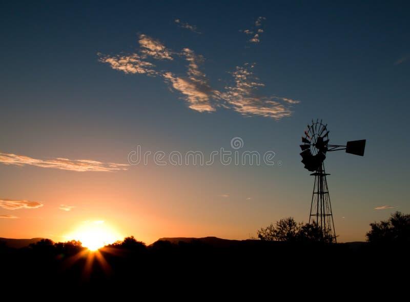 Silhouet van een Windmolen bij zonsondergang stock foto's