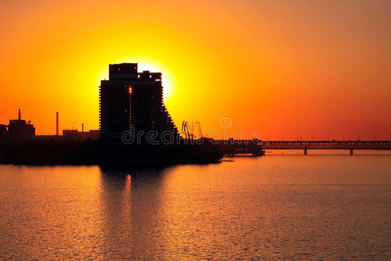 Silhouet van een wolkenkrabberzeil en een Oude brug op een zonsondergangachtergrond, op de Dnieper-Rivier in de Dnipro-stad stock foto's
