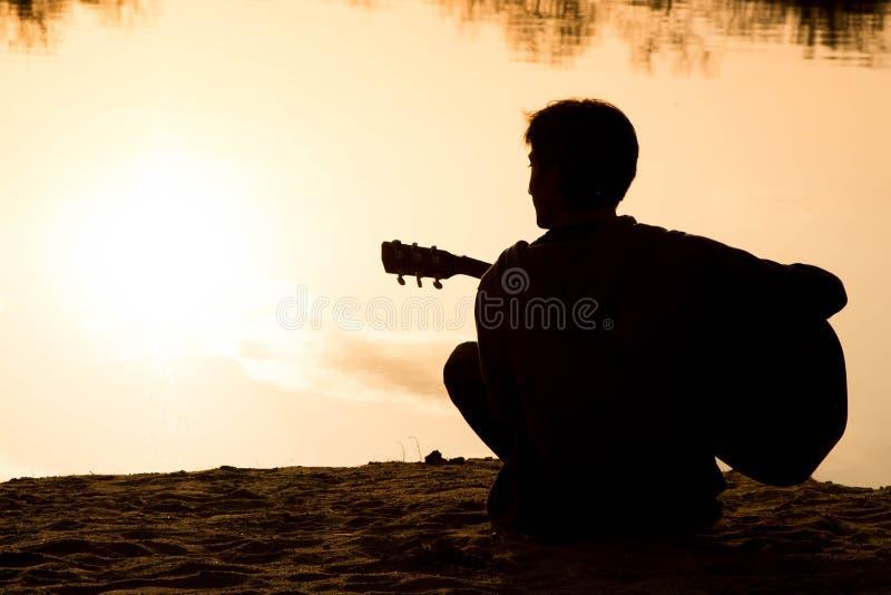 Silhouet van een zitting van de jonge mensen speelgitaar op het zand royalty-vrije stock foto