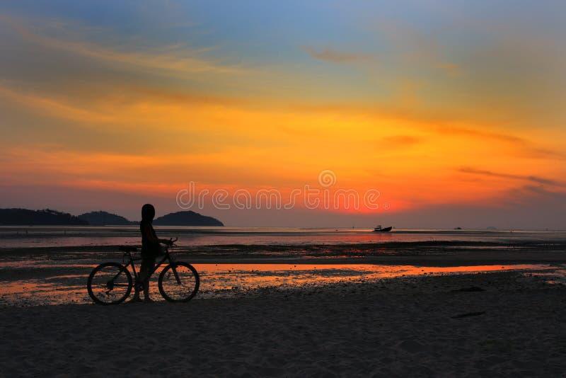 Silhouet van eenzaam niet geïdentificeerd meisje met fiets op strand met zonsonderganglicht stock afbeeldingen